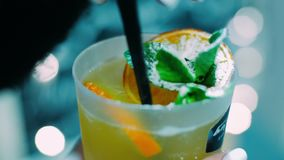 Alcoholic cocktail of fruits decorated with peppermint and powdered sugar. Fresh cocktail with mint leaves by adding of powdered sugar. Bar customer mixing stock video