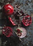 Alcoholic cocktail garnished with pomegranate seeds. On dark moody background royalty free stock photos