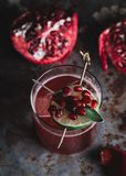 Alcoholic cocktail garnished with pomegranate seeds. On dark moody background stock images