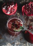 Alcoholic cocktail garnished with pomegranate seeds. On dark moody background stock photo