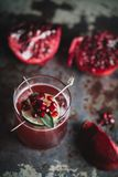 Alcoholic cocktail garnished with pomegranate seeds. On dark moody background royalty free stock photography