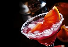 Alcoholic cocktail Greyhound, with vodka, liqueur, grapefruit juice and ice, black background, selective focus royalty free stock photography