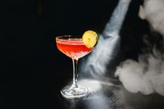 Alcoholic cocktail Greyhound, with vodka, liqueur, grapefruit juice and ice, black background, all in smoke, garnished stock photos