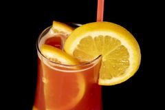 Alcoholic cocktail with lemons inside and lemon wedge on the glass with straw stock image