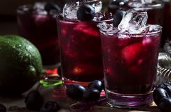 Alcoholic cocktail with liqueur, blueberry, lime juice, crushed ice, bar tools on black background, selective focus. Alcoholic cocktail with liqueur, blueberry stock image