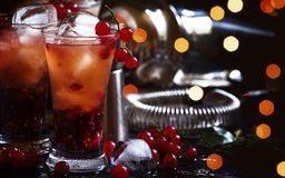 Alcoholic cocktail with liqueur, orange juice and red currant, black table, selective focus. Alcoholic cocktail with liqueur, orange juice and red currant, black stock photo