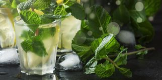 Alcoholic cocktail, mint tea with rum in small glasses with ice in a heart shaped vintage wood background, selective focus stock photo