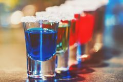 Alcoholic cocktail row on bar counter, colorful shooters cocktails drinks. Cocktails royalty free stock image