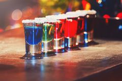 Alcoholic cocktail row on bar counter, colorful shooters cocktails drinks. Cocktail royalty free stock photo