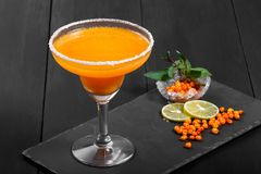 Alcoholic cocktail with sea buckthorn in a glass on dark background. Royalty Free Stock Image