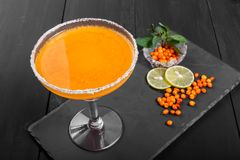 Alcoholic cocktail with sea buckthorn in a glass on dark background. Royalty Free Stock Photos