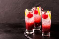 Alcoholic cocktail sour cherry gin or porch crawler. Alcoholic shot cocktail sour cherry gin or porch crawler with liqueur and lime. Black background. Horizontal Royalty Free Stock Images