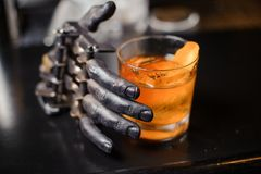 Alcoholic cocktail stands on bar stand, next to the decor - a molded arm of a steel color. Alcoholic cocktail of orange color in a crystal glass stands on a Stock Photography