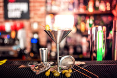 Alcoholic drink on bar counter. Dry martini with ice and olives, served cold in restaurant, bar or pub. Royalty Free Stock Image