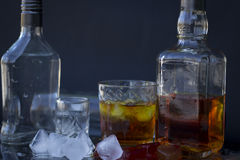 Alcoholic drink. A bottle of vodka and whiskey, vodka and whiskey with ice in a glass, red ice, alcoholic drink Stock Image