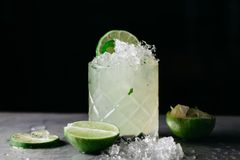 Summer alcoholic cocktail with crushed ice garnished with limes. Alcoholic drink with crushed on dark background royalty free stock photos