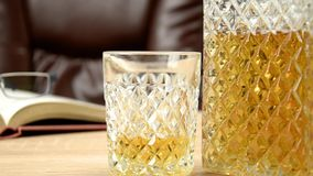 Alcoholic drink in crystal decanter. In a glass poured whiskey on a wooden table in the background a chair for seating. Open book stock video