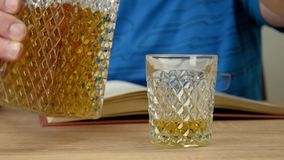 Alcoholic drink in crystal decanter. A man holds a glass in his hand and pours a whiskey drink. Open book with glasses. stock footage