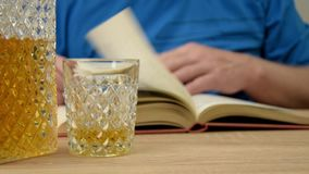 Alcoholic drink in crystal decanter. A man holds a glass in his hand and pours a whiskey drink. Open book with glasses. stock video footage