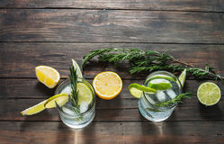 Alcoholic drink gin tonic cocktail with lemon, rosemary and ice on rustic wooden table, copy space. Stock Photo