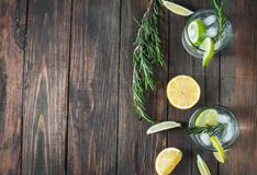 Alcoholic drink gin tonic cocktail with lemon, rosemary and ice on rustic wooden table, copy space Royalty Free Stock Image