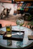 Alcoholic drink with lemon and ice on a old glas table royalty free stock photos