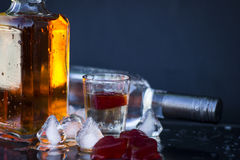 Alcoholic drink. Vodka bottle with glasses and a red ice, vodka and whiskey in glass with ice, alcoholic drinkk Stock Photos