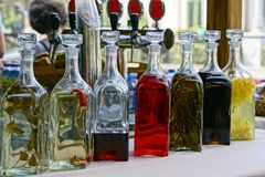 Closed glass bottles with colored drinks on the table royalty free stock photography