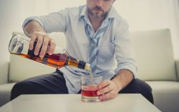 Alcoholic drunk Business man in loose time on couch drinking whisky Stock Photography