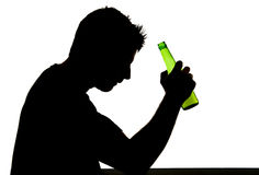 Alcoholic drunk man with beer bottle in alcohol addiction silhouette. Silhouette of alcoholic drunk man holding beer bottle in alcohol addiction and alcoholism Stock Photography