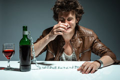 Alcoholic drunk man drinking wine, feeling depressed, falling into addiction problem Royalty Free Stock Image