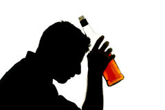 Alcoholic drunk man with whiskey bottle in alcohol addiction silhouette. Silhouette of alcoholic drunk man holding whiskey bottle in alcohol addiction and royalty free stock photo