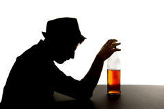 Alcoholic drunk man with whiskey bottle in alcohol addiction silhouette Royalty Free Stock Images