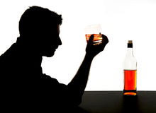 Alcoholic drunk man with whiskey glass in alcohol addiction silhouette. Silhouette of alcoholic drunk man holding whiskey glass in alcohol addiction and Stock Photo