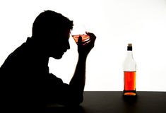 Alcoholic drunk man with whiskey glass in alcohol addiction silhouette. Silhouette of alcoholic drunk man holding whiskey glass in alcohol addiction and royalty free stock images