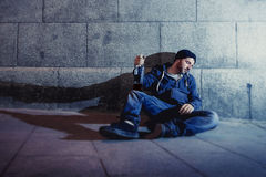 Alcoholic grunge man sitting on ground street corn Royalty Free Stock Images