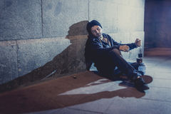 Alcoholic grunge man sitting on ground street corner drinking alcohol bottle Royalty Free Stock Image