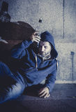Alcoholic grunge man sitting on ground street corner drinking alcohol bottle Royalty Free Stock Photos