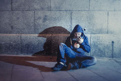 Alcoholic grunge man sitting on ground street corner drinking alcohol bottle Royalty Free Stock Images