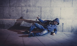 Alcoholic grunge man sitting on ground street corner drinking alcohol bottle Stock Image