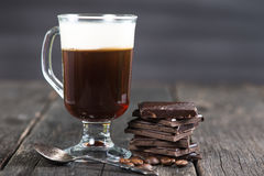 Alcoholic irish coffee with dark chocolate and caffee beans Royalty Free Stock Photos
