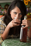 Alcoholic Latina Woman. At Home with Liquor Bottle Royalty Free Stock Photography