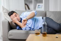Alcoholic lying on sofa and looking at wristwatch. Alcoholism, alcohol addiction and people concept - male alcoholic lying on sofa and looking at wristwatch Royalty Free Stock Image