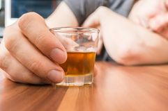 Alcoholic man is sleeping on table. Glass with alcohol in hand Stock Images