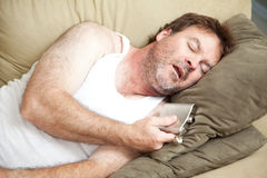 Alcoholic Passed Out Drunk. Unemployed man passed out drunk on the couch with a flask of booze in his hand royalty free stock images