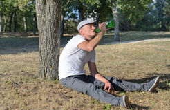Alcoholic sitting drinking in a park Stock Photography