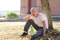 Alcoholic sitting thinking Royalty Free Stock Photography