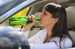 Alcoholic woman drinking a driving stock photo