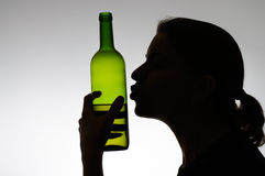 Alcoholic woman kissing a wine bottle Royalty Free Stock Images