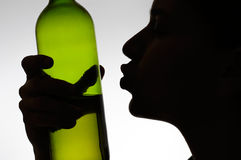 Alcoholic woman kissing a wine bottle Stock Images